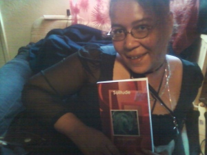 Sumiko Saulson holding a copy of her book Solitude