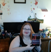 "Kateryna Fury - holding a copy of Sumiko Saulson's ""Warmth."""