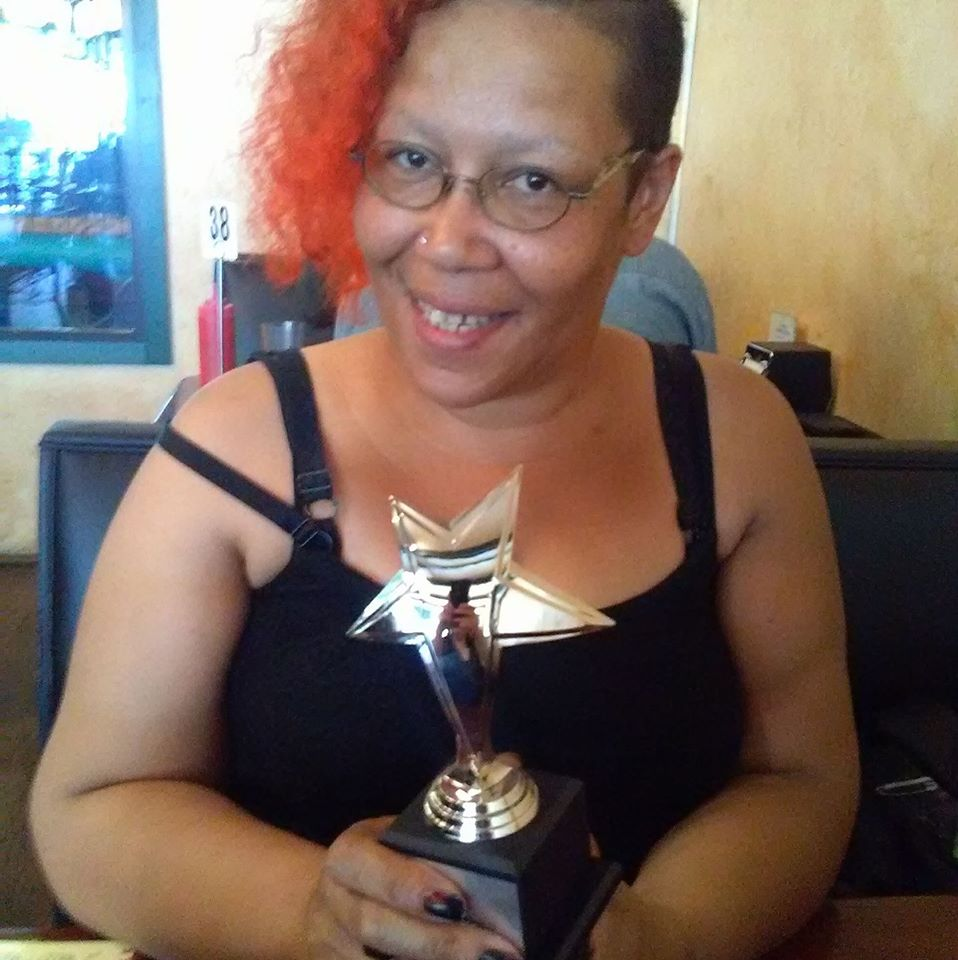 Author Sumiko Saulson (an African American nonbinary person with orange hair) holding a star shaped Mixy Award in hir hands
